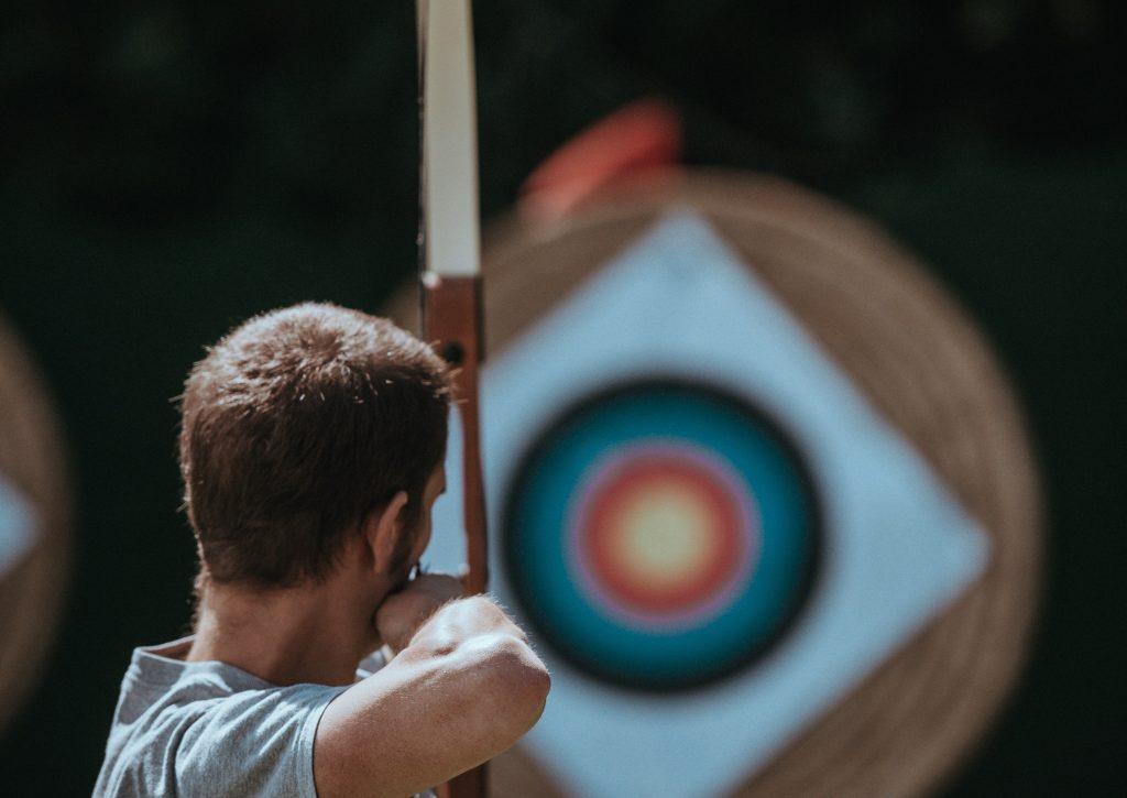 Bogenschütze, der auf Zielscheibe zielt.